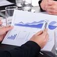 businessman-holding-pen-over-graph-business-meeting-sitting-desk-43434410