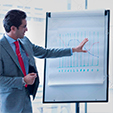 businessman-leading-meeting-at-flip-chart-in-conference-room-G1TCD3